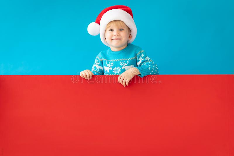 Happy child holding red Christmas banner blank against blue background. Happy child holding red banner blank against blue background. Christmas greeting card stock photo