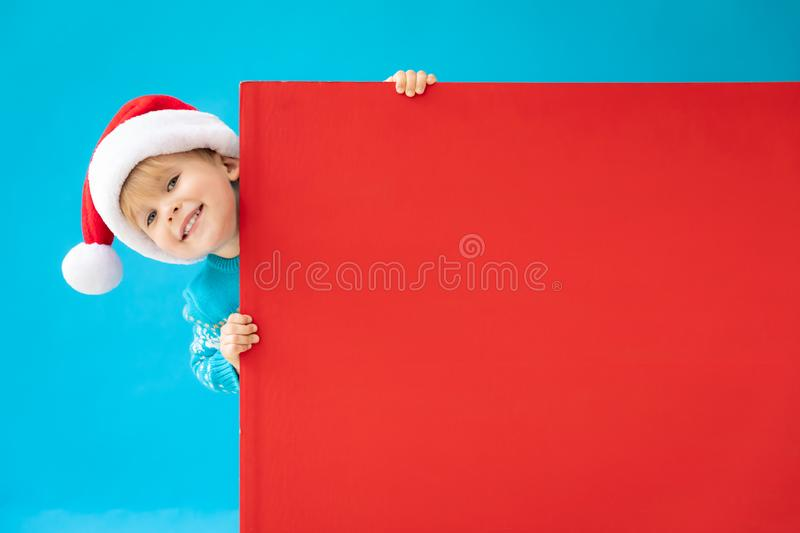 Happy child holding red Christmas banner blank against blue background. Happy child holding red banner blank against blue background. Christmas greeting card stock image