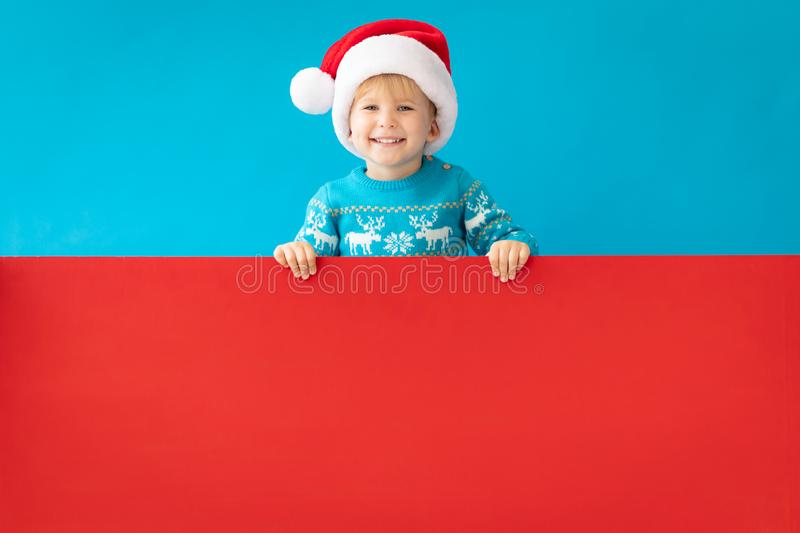 Happy child holding red Christmas banner blank against blue background. Happy child holding red banner blank against blue background. Christmas greeting card stock photography