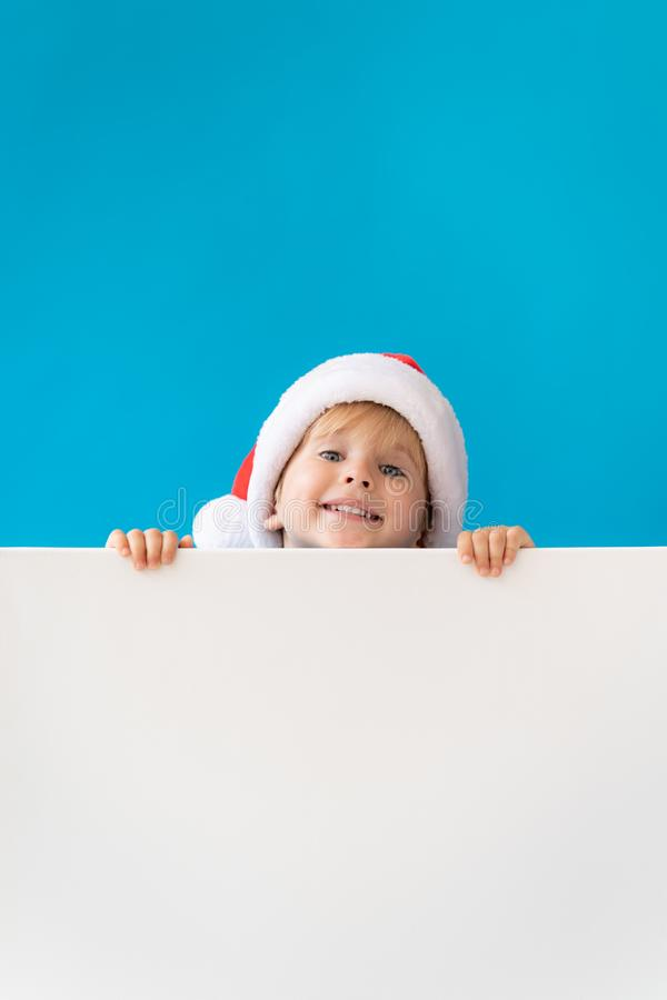 Happy child holding white Christmas banner blank against blue background. Happy child holding white banner blank against blue background. Christmas greeting card stock images