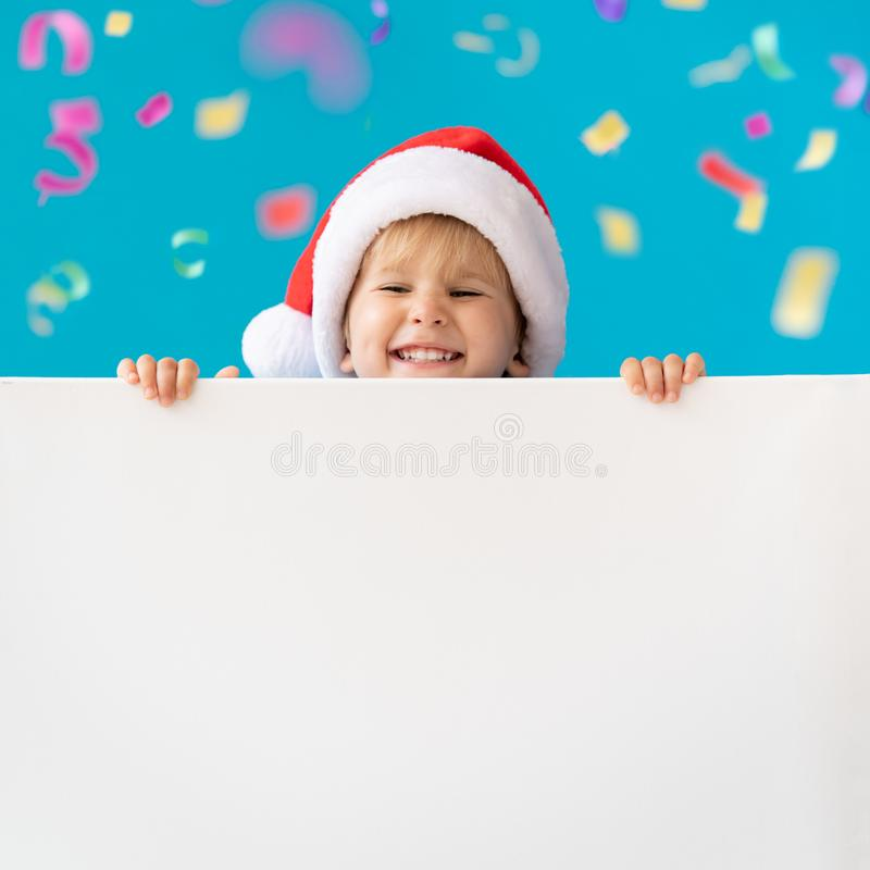 Happy child holding white Christmas banner blank against blue background. Happy child holding white banner blank against blue background. Christmas greeting card stock photos