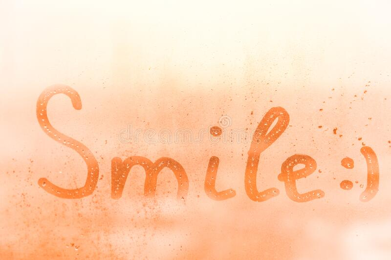 The happy child inscription smile on the orange or pink evening or morning window glass stock image