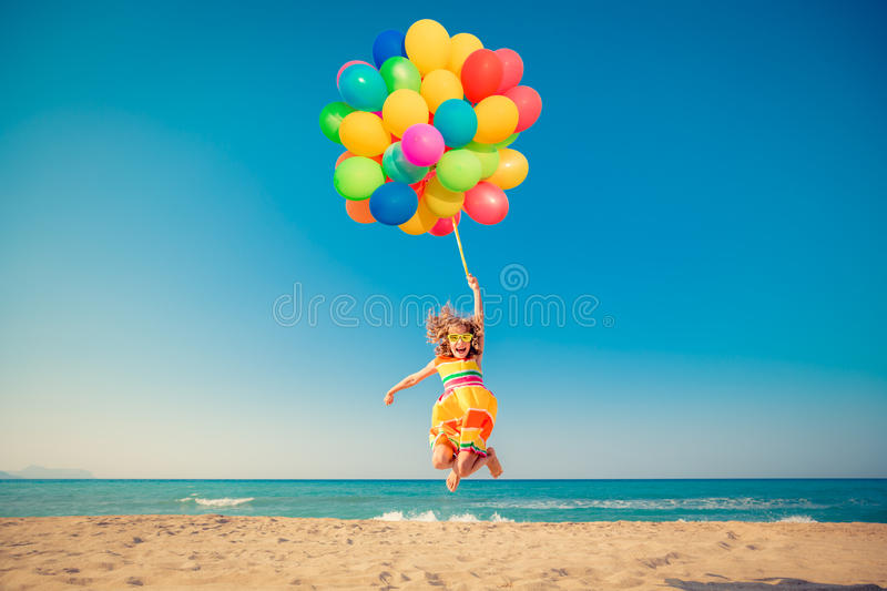 Happy child jumping with colorful balloons on sandy beach stock photos