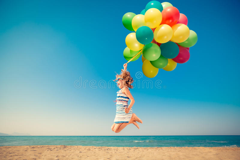 Happy child jumping with colorful balloons on sandy beach royalty free stock images