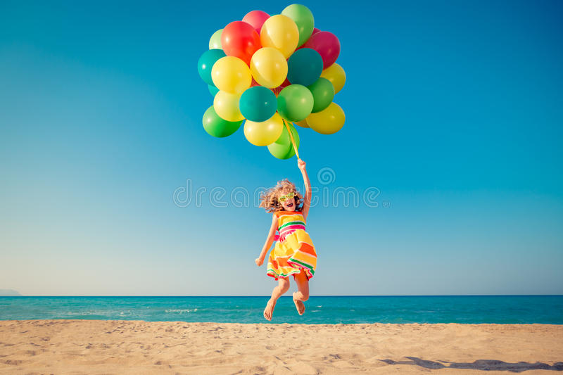 Happy child jumping with colorful balloons on sandy beach stock images