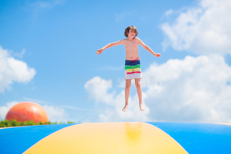 Happy Child Jumping On A Trampoline Stock Photo