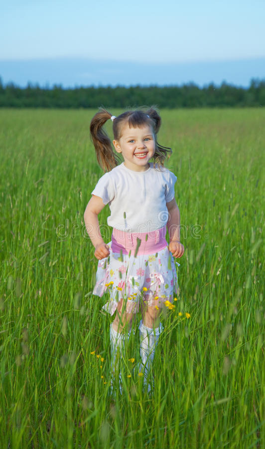 Happy child jumps on green grass in field royalty free stock photography