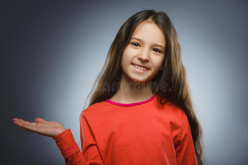 Happy child keeps on hand something. Closeup Portrait of handsome girl smiling stock photos