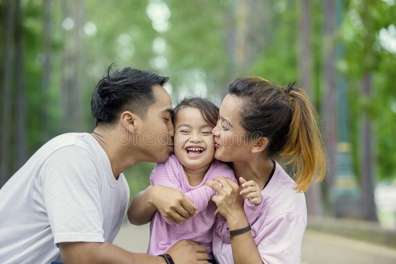 Happy child kissed by her parents in the park stock photos