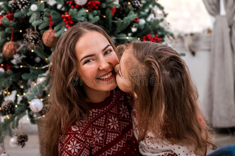 Happy child kissing her mother near fir-tree royalty free stock images