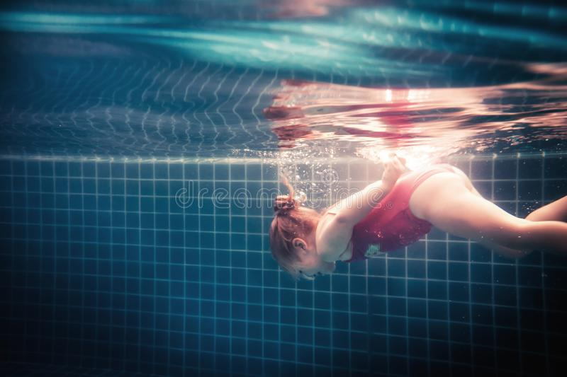 Happy child learning swimming underwater in swimming pool during diving training stock images