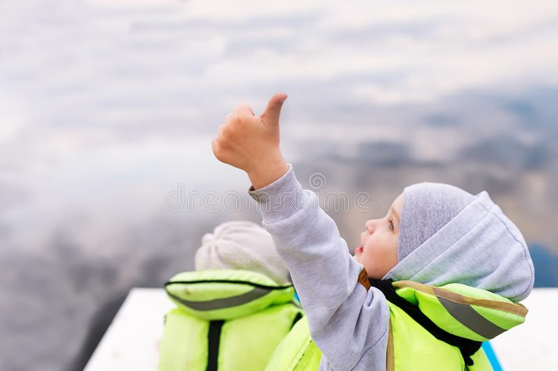 Happy child in lifejacket on the boat showing good. Ok gesture thumb up gunny happy boy. Closeup photo royalty free stock image