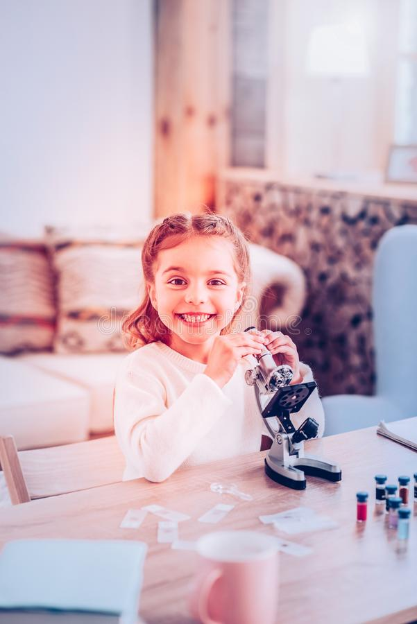 Happy child liking personal lesson of Biology. Lesson of Biology. Happy child in sweater liking personal lesson of Biology while using modern microscope stock images
