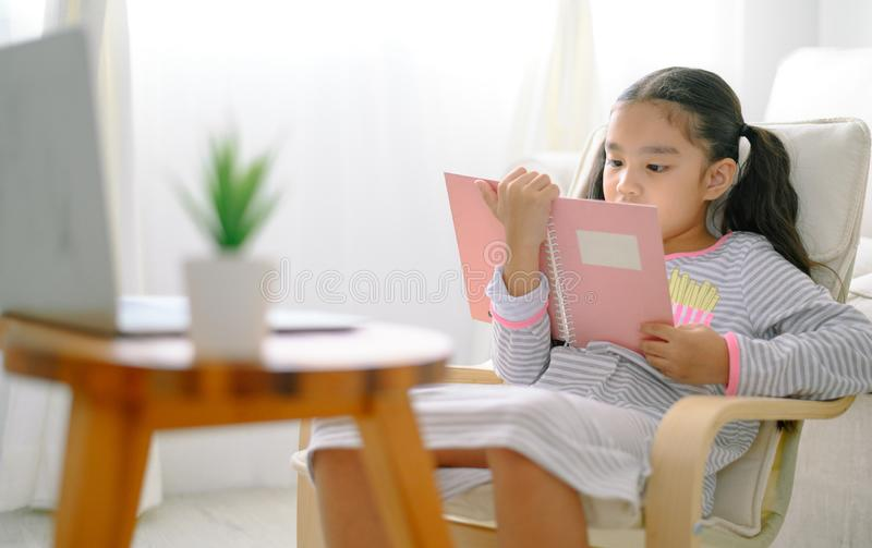 Happy child little asian girl  reading a books on the table in the living room at home. family activity concept royalty free stock image