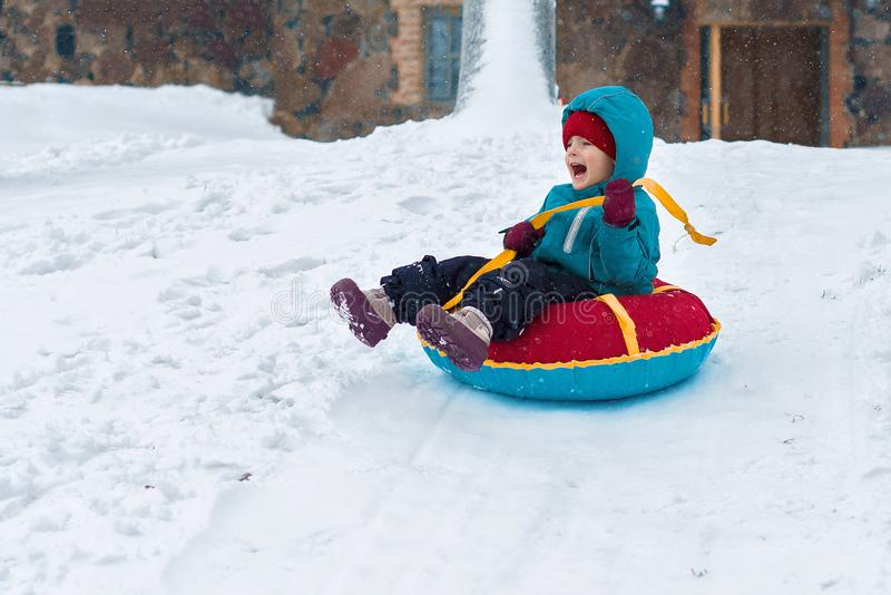Happy child. little boy in winter ride on a sled from the mountain. Kid long and happy smiles royalty free stock photos