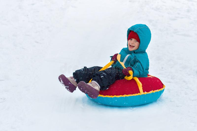 Happy child. little boy in winter ride on a sled from the mountain. Kid long and happy smiles royalty free stock image