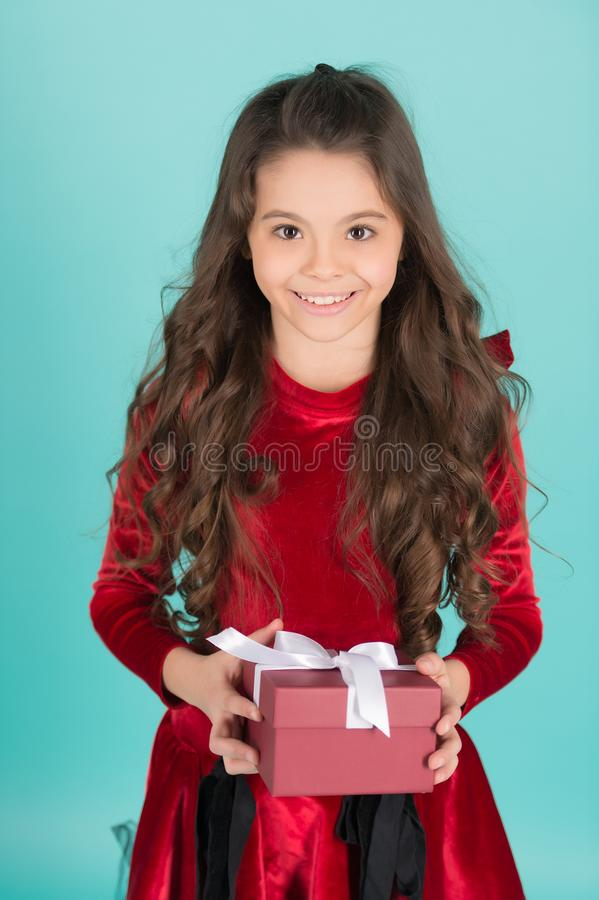 Happy child with long brunette hair hold present box. Happy child with long brunette hair in red dress hold present box on blue background. Birthday, new year stock image