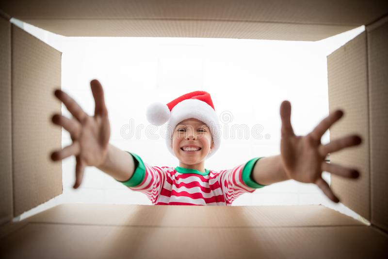 Surprised child unpack Christmas gift box royalty free stock photography