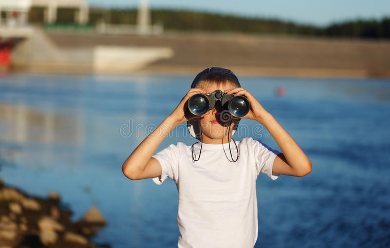 Happy child looking in nautical binoculars against blue water background. Kid having fun on nature. Summer sea dream and imaginat stock image
