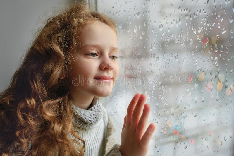 Happy child looking out the window with wet glass autumn bad weather. royalty free stock photography
