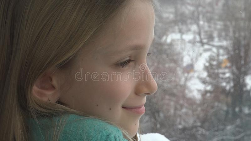 Happy Child Looking on Window, Kid Girl Dreaming Snowball Fight, Snowman Winter royalty free stock images