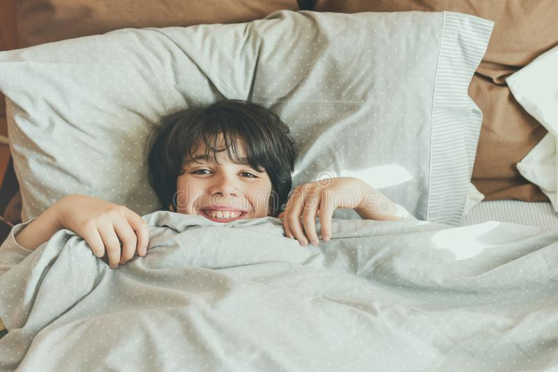 Happy child lying on the bed stock images