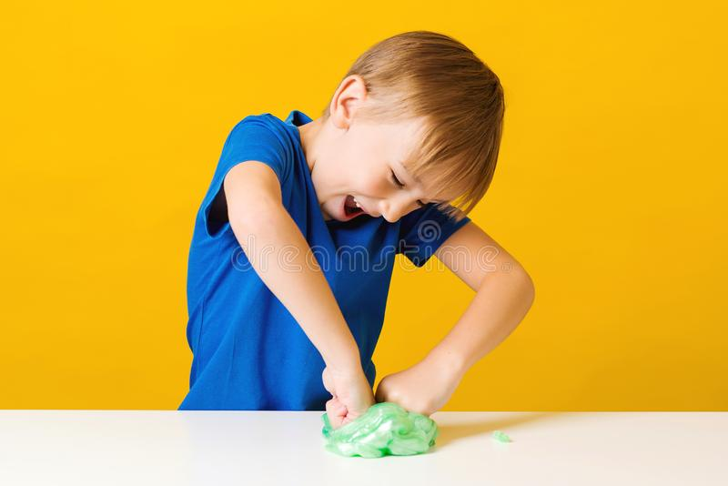 Happy child making homemade slime toy. Funny kid plays with trendy slime at home. Happy childhood royalty free stock images