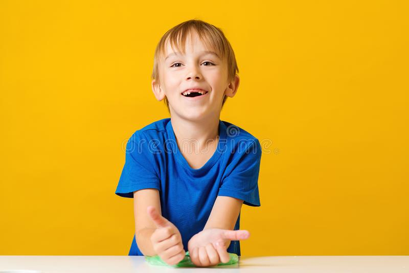 Happy child making homemade slime toy. Funny kid plays with trendy slime at home. Happy childhood. Time for experiment royalty free stock image