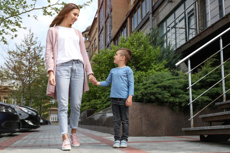 Happy child and mother holding hands outdoors, low angle view stock images