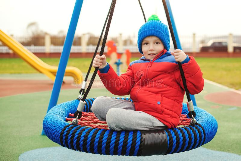 Happy child at outdoors playground. Funny kid boy having fun at park. Smiling boy swinging on modern swing. Child wearing red royalty free stock photo