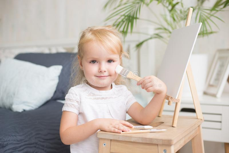 Happy child painting with gouache and watercolor paints on the easel indoors. stock photography