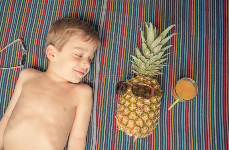Happy child and pineapple sunbathing over a towel royalty free stock images