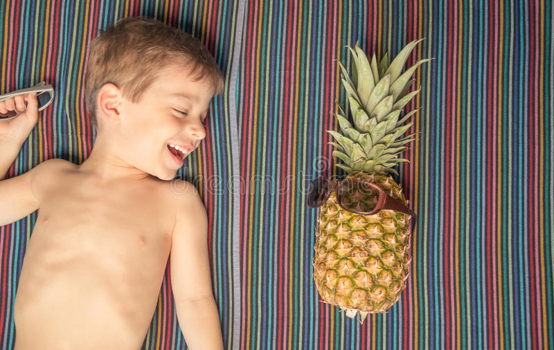 Happy child and pineapple sunbathing over a towel stock photos