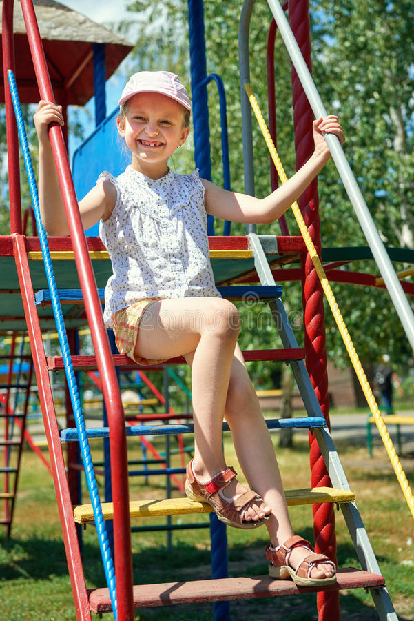 Happy child on playground outdoor, play in city park, summer season, bright sunlight stock image