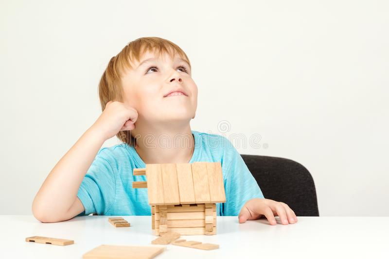 Happy child playing and building wooden home. Childhood dreams. Little boy builds his dream house. Happy life, house or mortgage. Investment concept stock images
