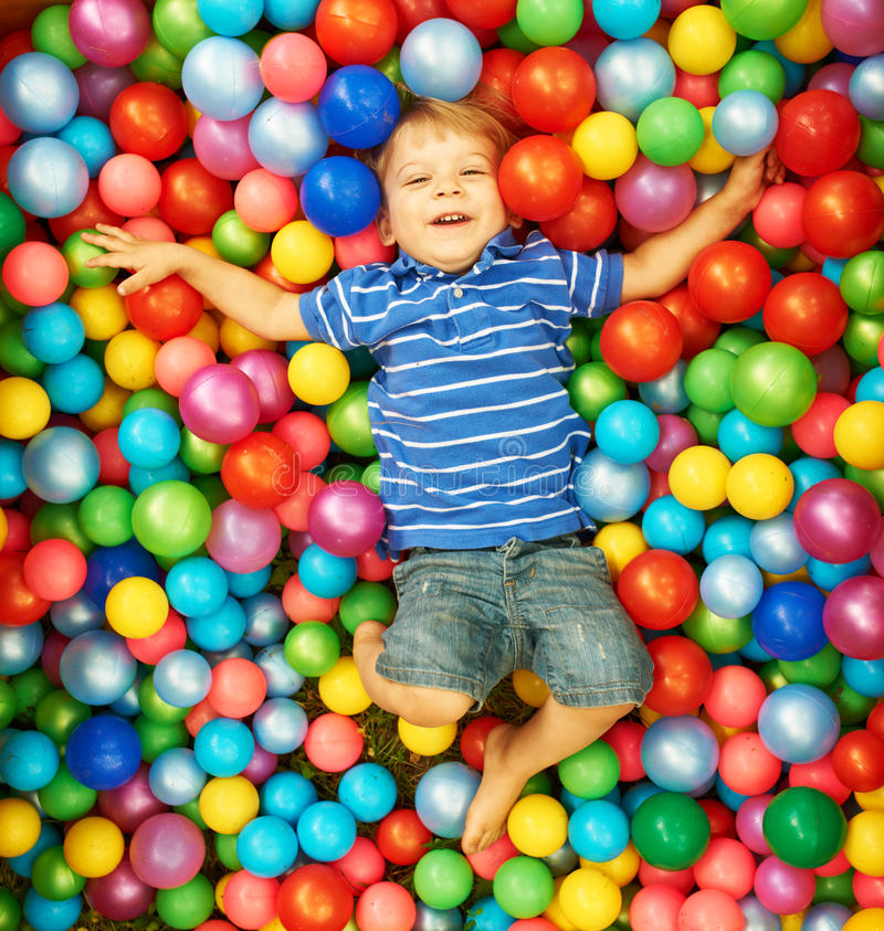 Happy child playing with colorful plastic balls. Happy child playing at colorful plastic balls playground high view stock image
