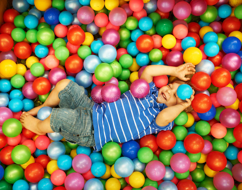 Happy child playing with colorful plastic balls. Happy child playing at colorful plastic balls playground high view royalty free stock images
