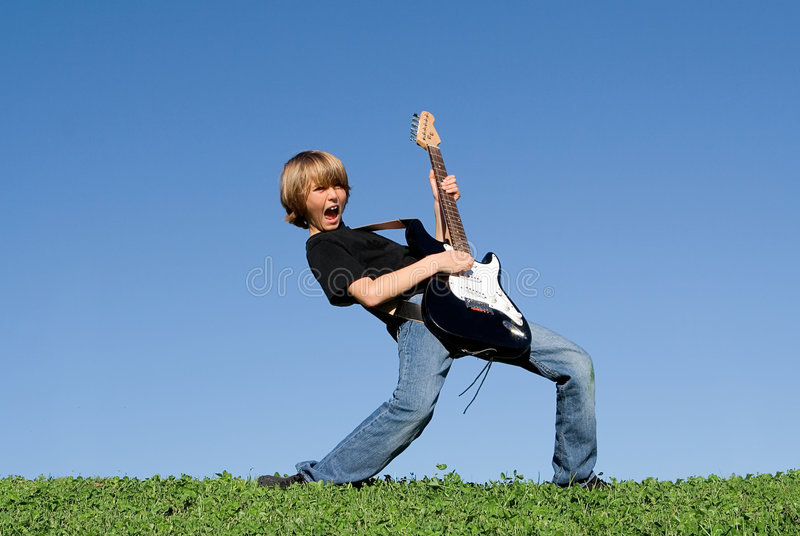 Happy child playing guitar royalty free stock photography