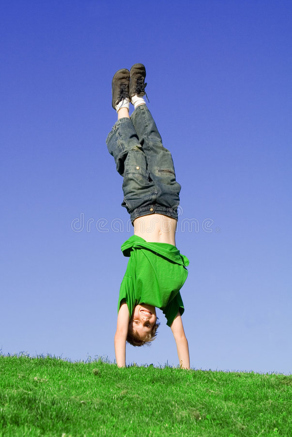 Happy child playing handstand stock photos