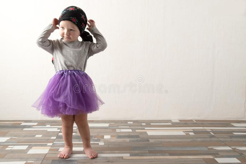 Happy child playing at home. The funny guy put on his sister`s skirt and admires himself. The concept of carefree childhood. Copy royalty free stock image