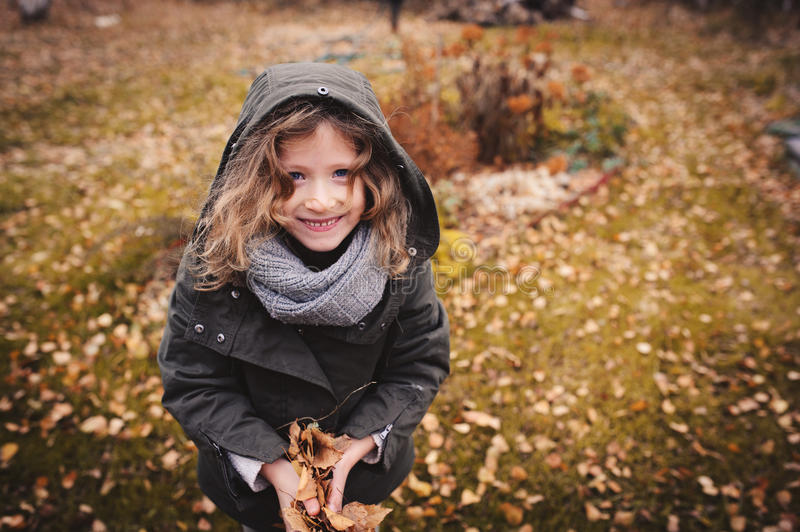 Happy child playing with leaves in autumn. Seasonal outdoor activities with kids. Lifestyle capture on the walk stock images