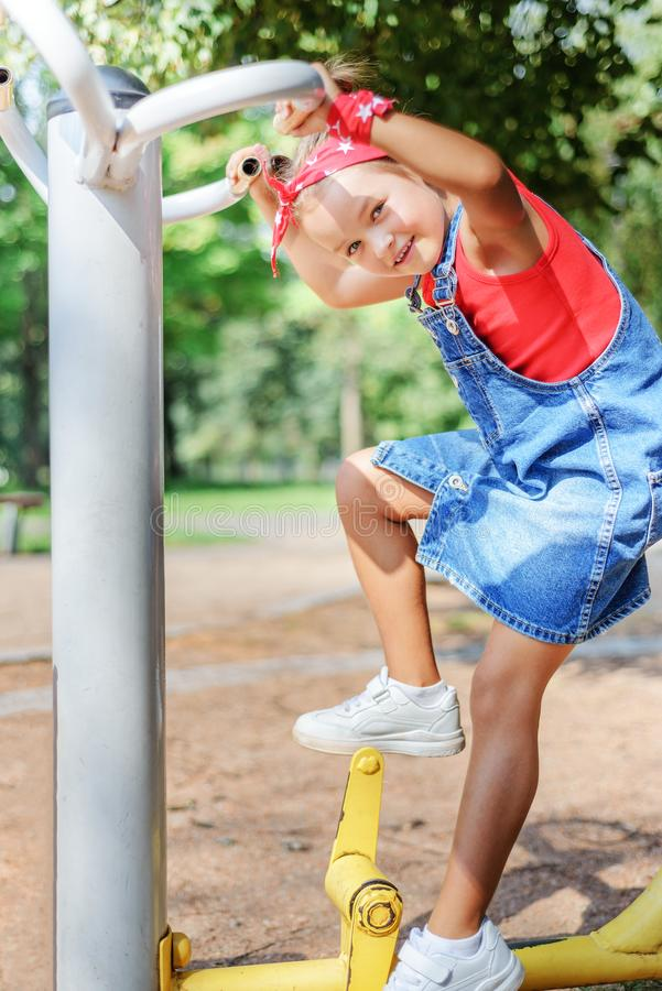 Happy child playing in the playground. little girl in denim overalls walks on a stepper simulator.  royalty free stock photo