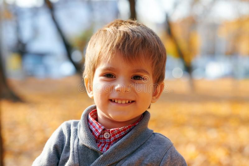 Happy child playing, posing, smiling and having fun in autumn city park. Bright yellow trees and leaves royalty free stock photo