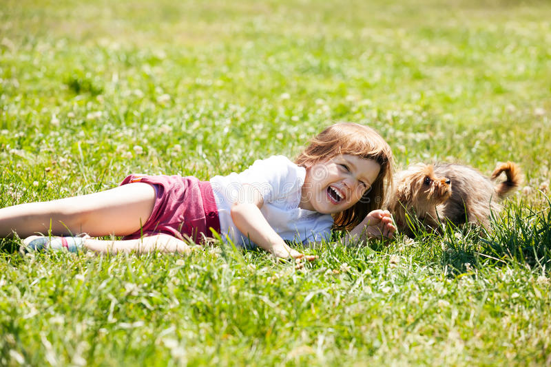 Happy child playing with puppy at meadow in summer. Happy three year old child playing with puppy at grass meadow in summer stock photo