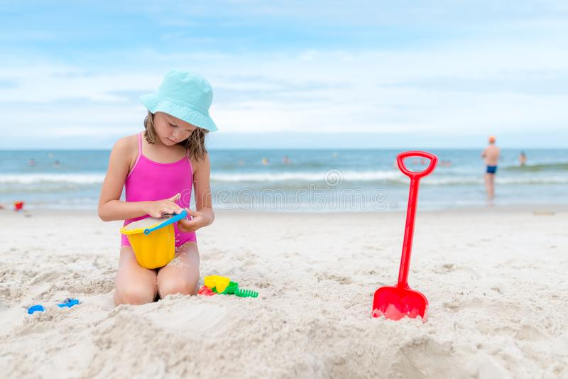 Happy child playing with sand at the beach in summer royalty free stock images