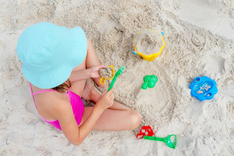 Happy child playing with sand at the beach in summer stock images
