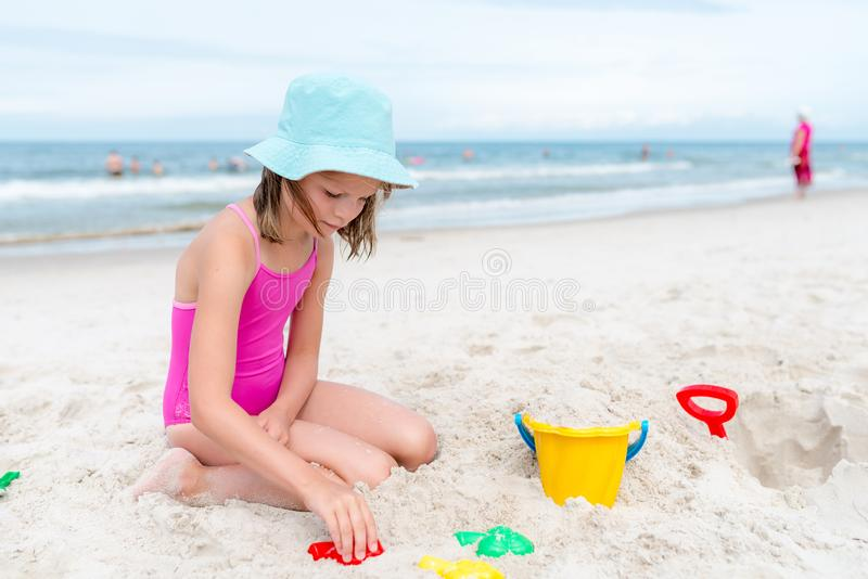 Happy child playing with sand at the beach in summer stock photo