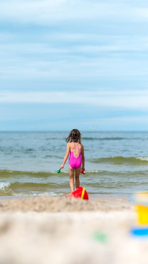 Happy child playing with sand at the beach in summer royalty free stock photos