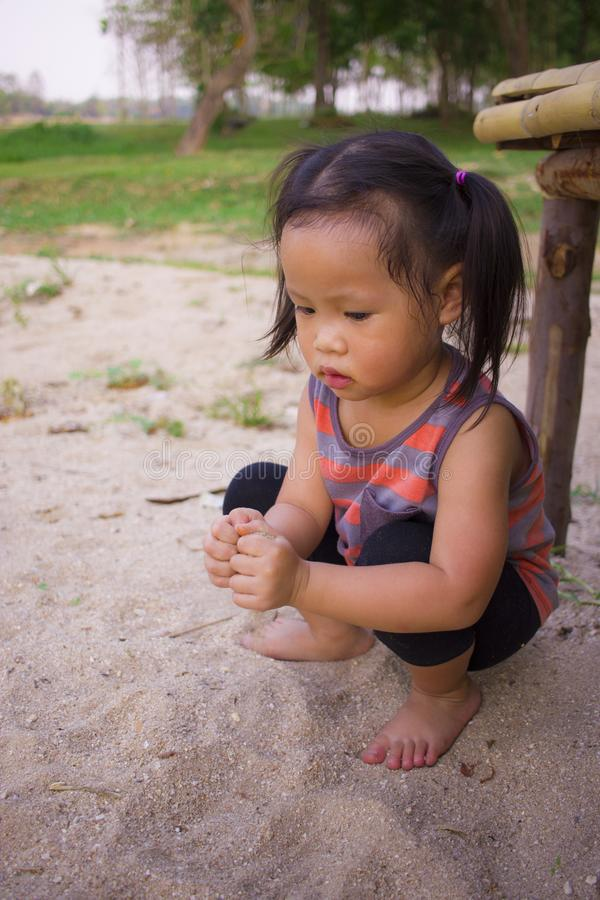 Happy child playing with sand, Funny Asian family in a park royalty free stock photography