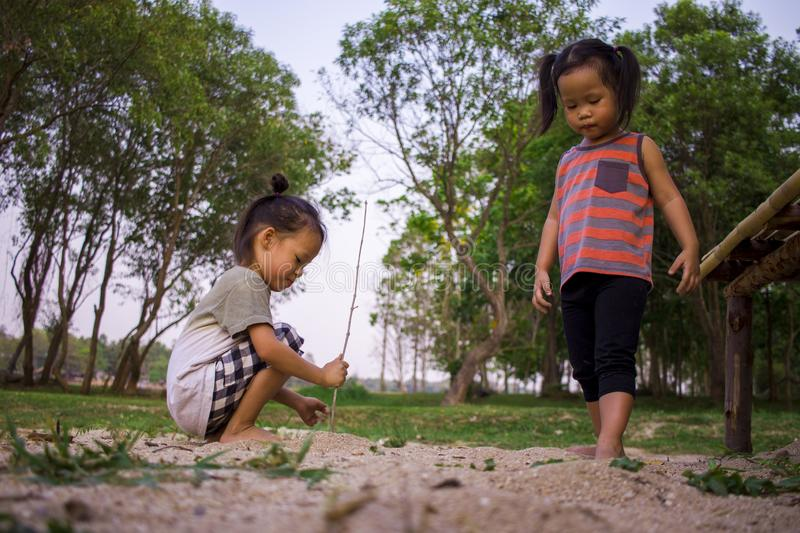 Happy child playing with sand, Funny Asian family in a park royalty free stock photo